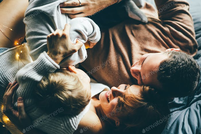 Young parents and cute baby lying together.