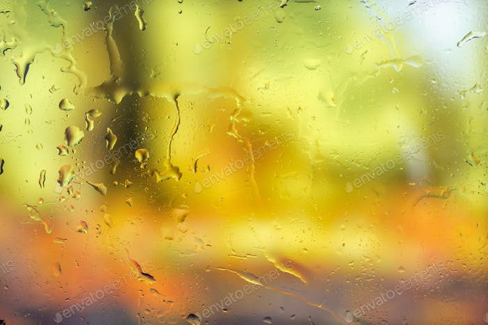 Autumn background. Drops of rain on the wet window and autumn colors of red orange and yellow