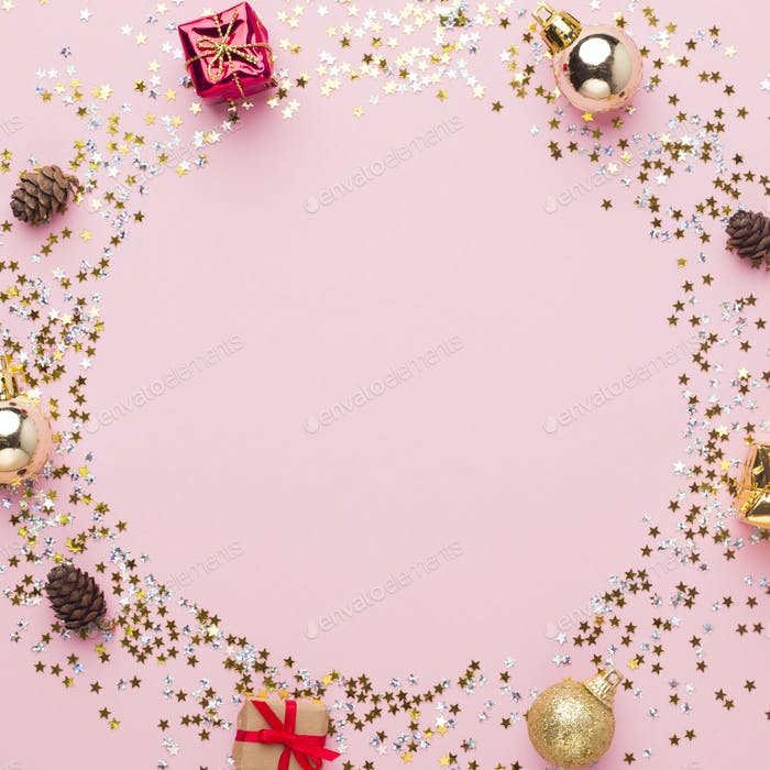 Round festive frame of decorations, gifts and confetti on pink