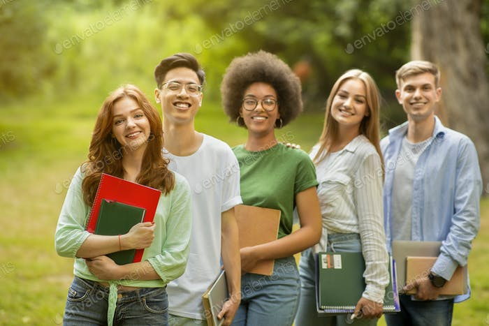 Group portrait of multiracial university students posing with workbooks outdoors at campus