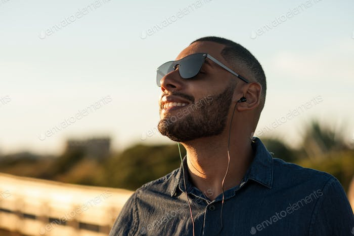 Latin man using earphones to listen music or motivational podcasts and enjoying the sunset