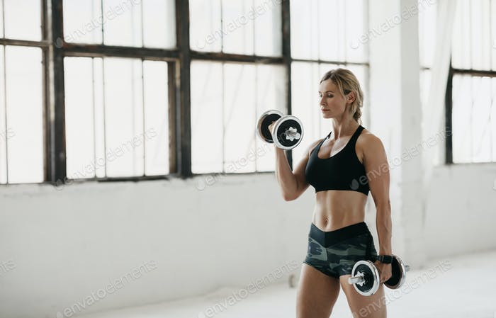 Exercises for biceps. Adult muscular woman in sportswear with fitness tracker doing exercises for