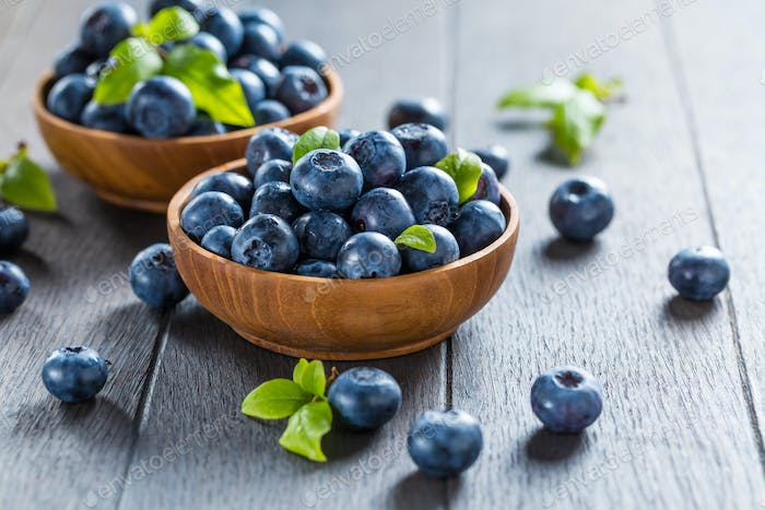 Fresh organic blueberry in bowl on wooden background