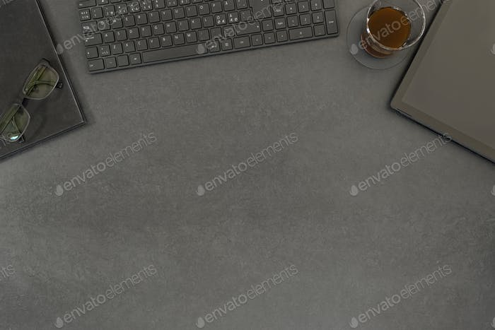 Top view of contemporary black concrete office desk with computer and supplies