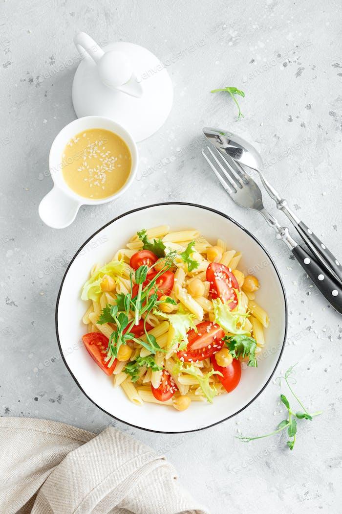 Nudelsalat mit frischen Tomaten, Kichererbsen, Salat und Erbsenkohl in der Mittagschüssel