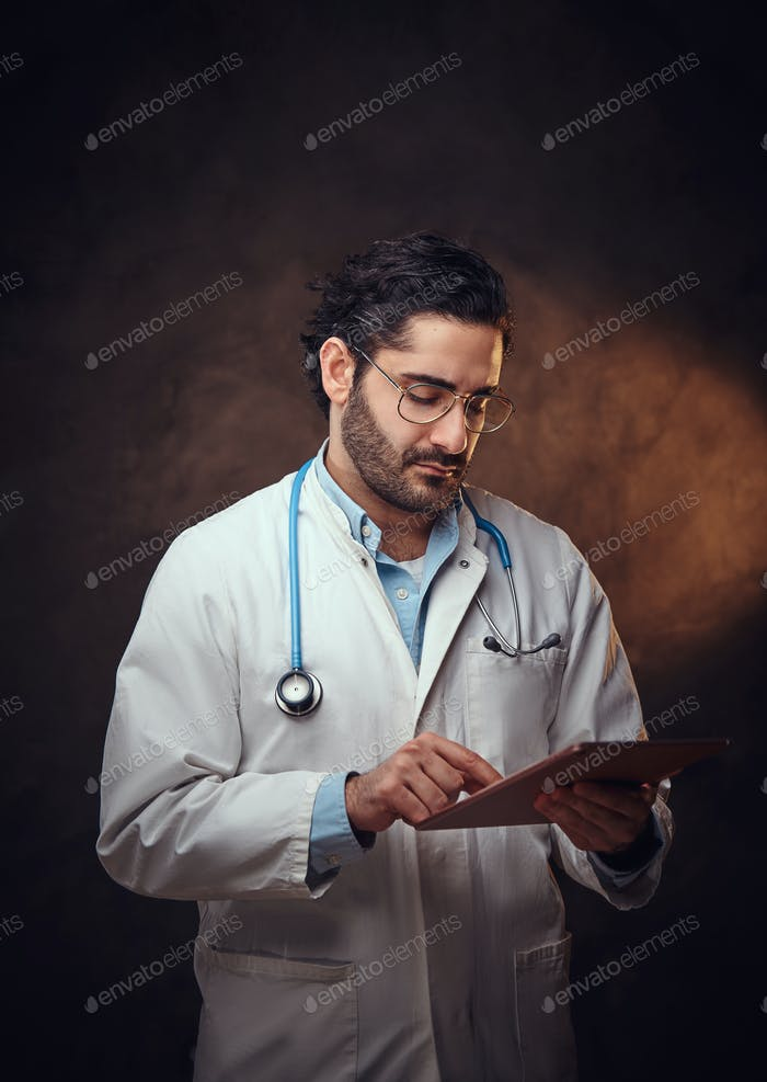 Portrait of focused doctor with tablet in hands