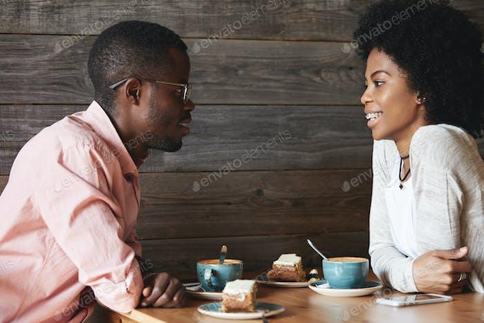 Glückliches dunkelhäutiges Paar, das nach langer Trennung ein nettes Gespräch hat und sich gegenseitig anschaut