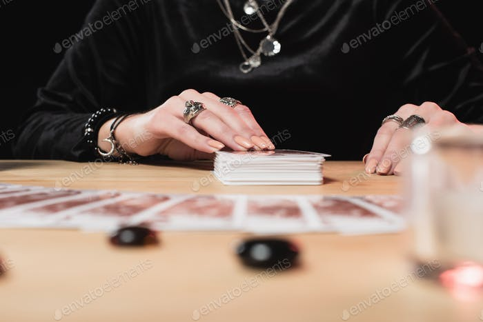 selective focus of  female psychic laying tarot cards near divination stones