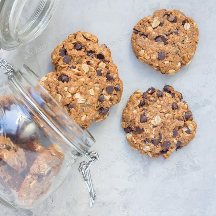 Glutenfreie Erdnussbutter, Haferflocken und Schokoladenstückchen im Glas, Draufsicht