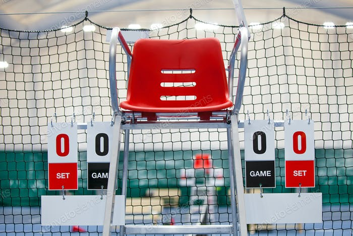 Umpire chair with scoreboard on a tennis court before the game.