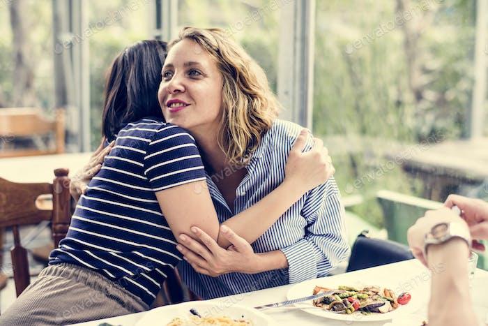 Friends hugging at a restaurant