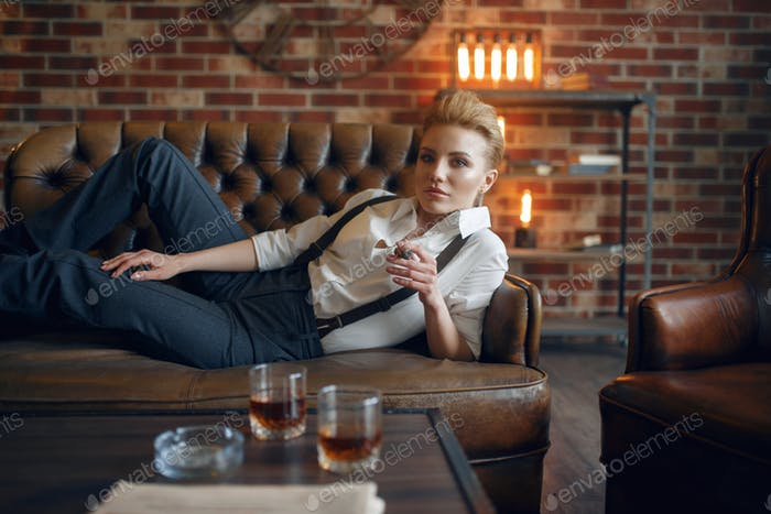 Woman lying on leather couch and smoking cigar