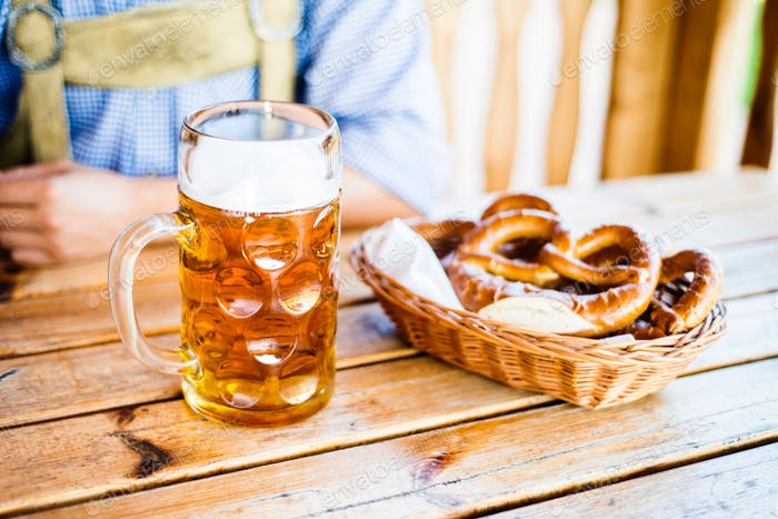 Man in traditional bavarian clothes with beer and pretzels