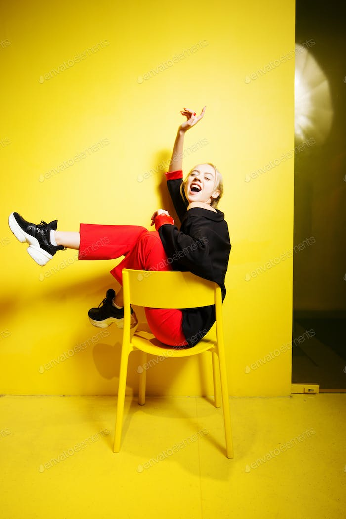 Young fashion girl blogger dressed in red trousers and black jacke possing sitting on the stool in