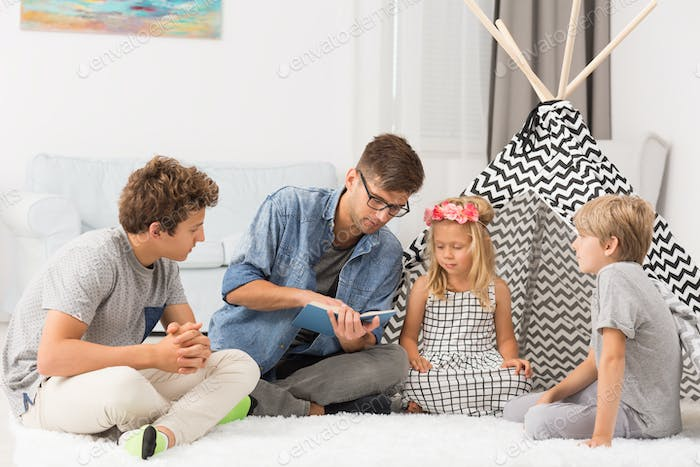 Children listening to their dad reading
