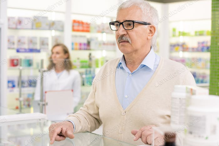 Senior client of drugstore standing by counter and waiting for pharmacist