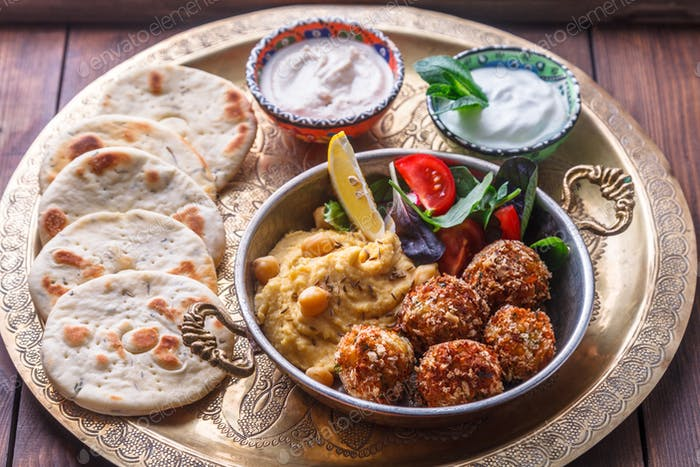 Hummus, falafel, salad and pita in a copper pan