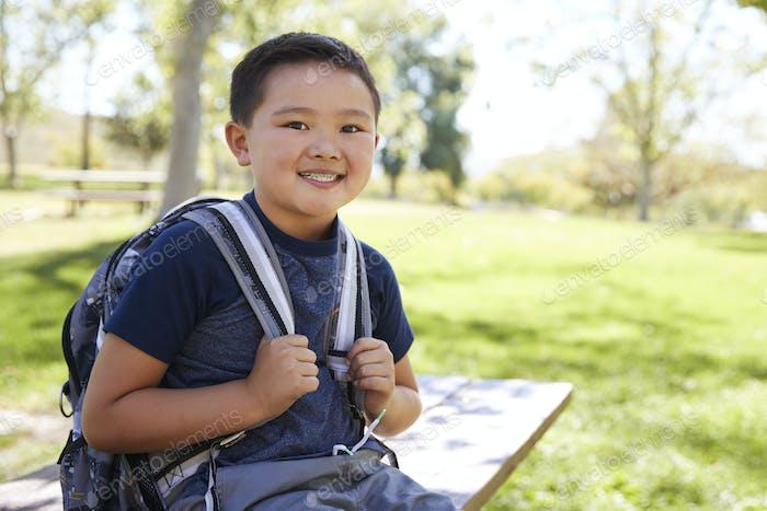 jóvenes asiático colegial con mochila sonriendo a cámara