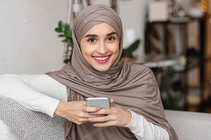 Portrait of happy muslim girl in hijab using smartphone at home