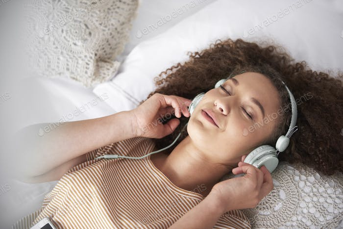 Teenage girl listening to music and lying on the bed