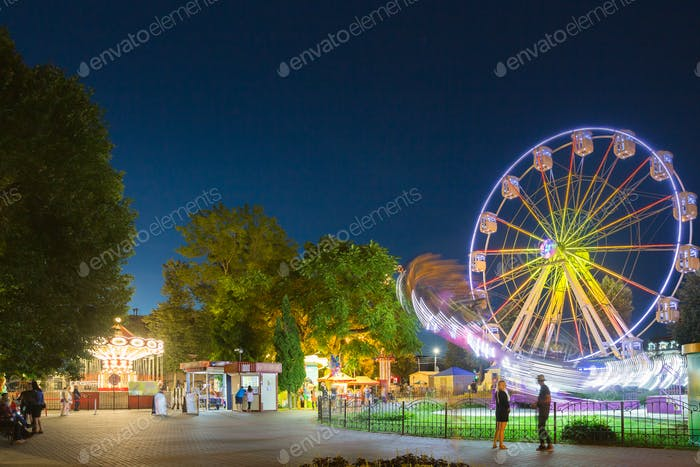 Attraction Ferris Wheel In Motion And Brightly Carousel Merry-Go