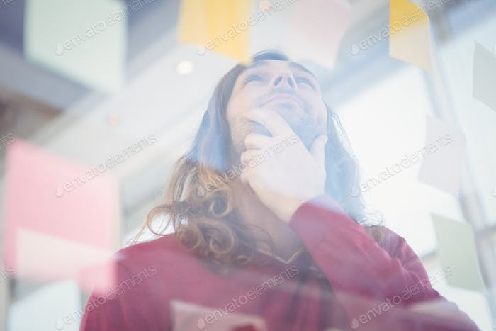 Low angle view of thoughtful hipster looking at sticky note stuck on glass in office