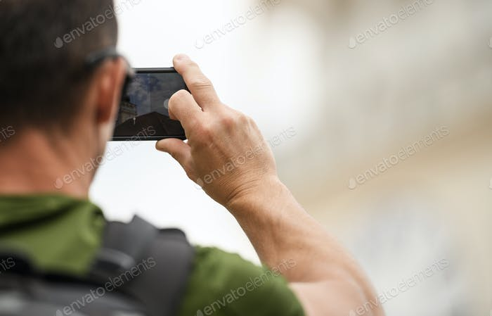 Men with Backpack Taking Pictures Using His Smartphone