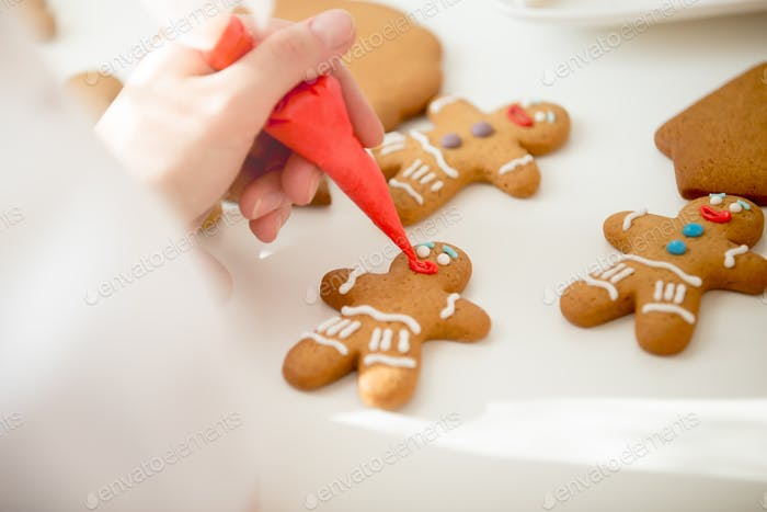 Close up of confectioner hand decorating a gingerman
