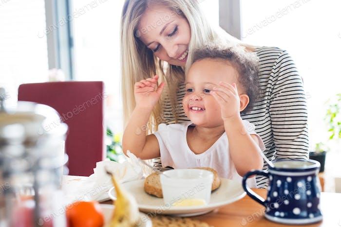 Schöne junge Mutter mit seiner Tochter zum Frühstück.