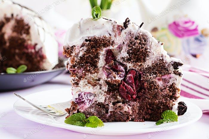 Schokoladenkuchen mit Kirschen und Sahne auf hellem Hintergrund.