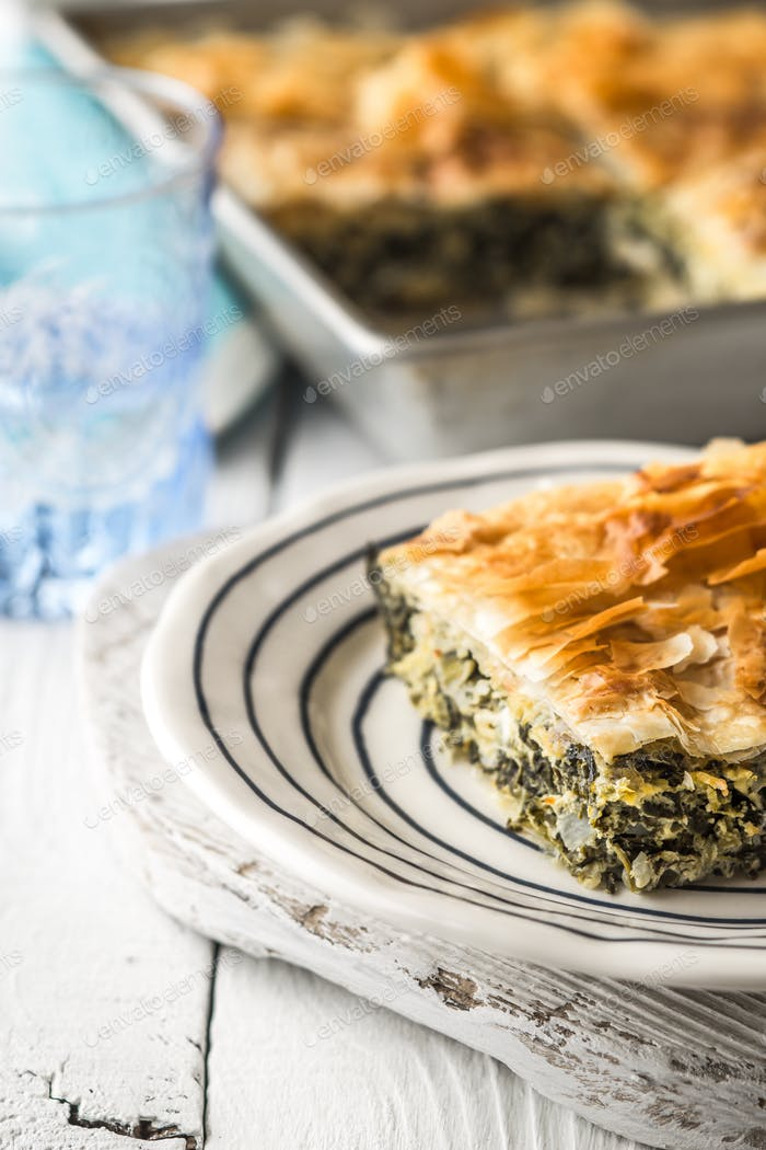 Greek pie spanakopita in the ceramic plate on the white  table  vertical