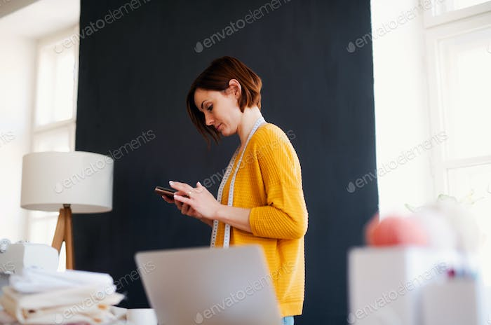 Young creative woman in a studio, using smartphone. A startup of tailoring business.
