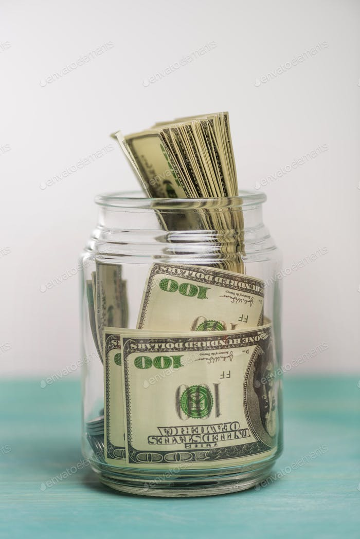 Close-up view of dollar banknotes in glass jar, donation concept