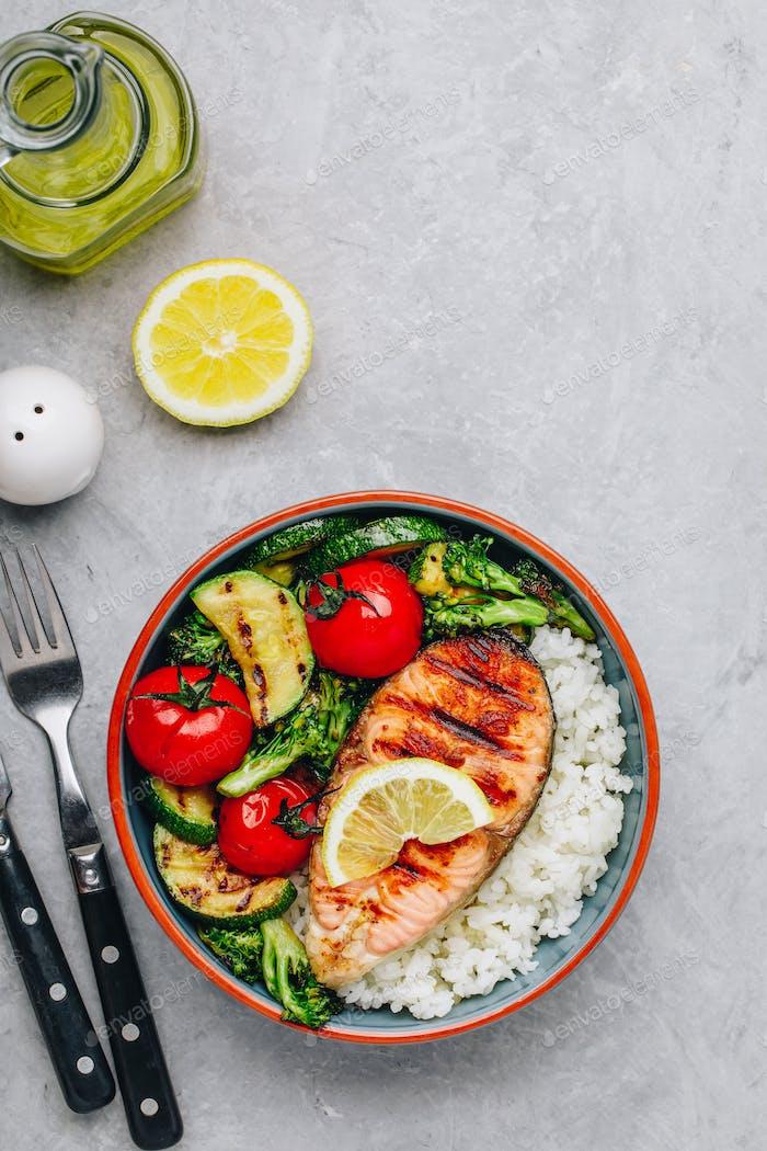 Gegrilltes Lachssteak mit Reis, Zucchini, Brokkoli, Tomaten.