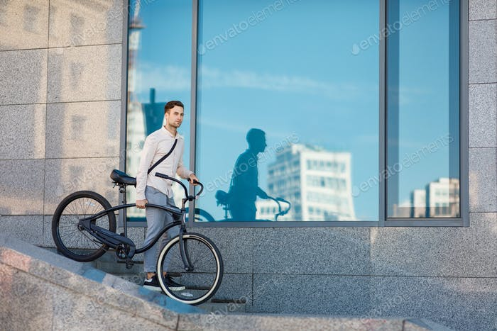 Short way to work. Young man walking down the stairs with bicycle