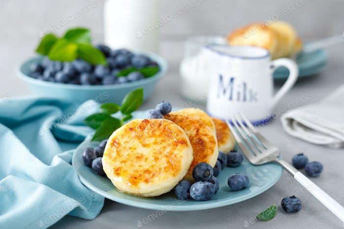 Hüttenkäse Pfannkuchen, süße Quark Krapfen mit Beeren, Syrniki mit Honig und frischer Heidelbeere