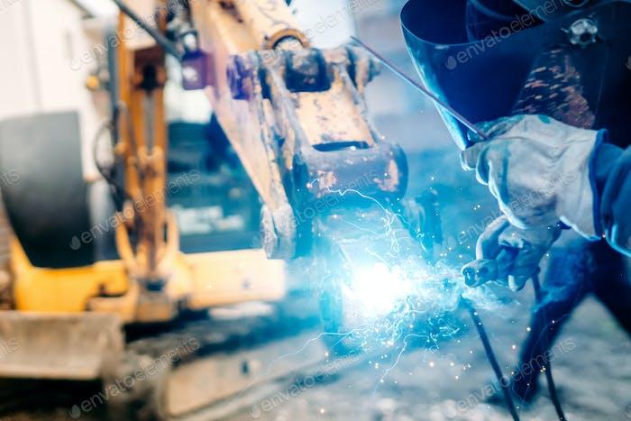 Mechaniker, Schweißer auf Baustelle. Reparaturschweißen erfolgt an indsutrialen Maschinen