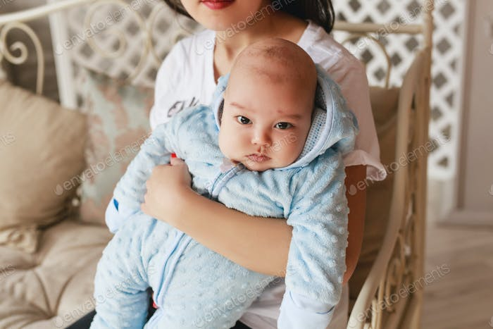 Happy asian mother holding adorable child baby boy.