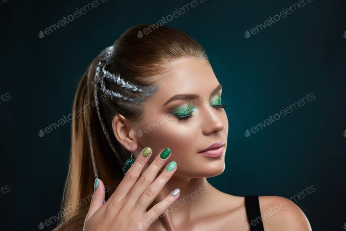 Beautiful brunette girl with stylish hairstyle and green shiny makeup