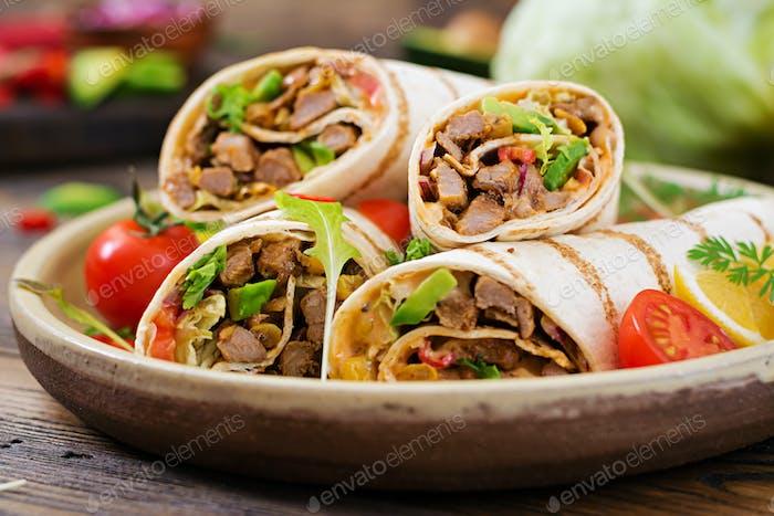 Burritos wickelt mit Rindfleisch und Gemüse auf einem hölzernen Hintergrund