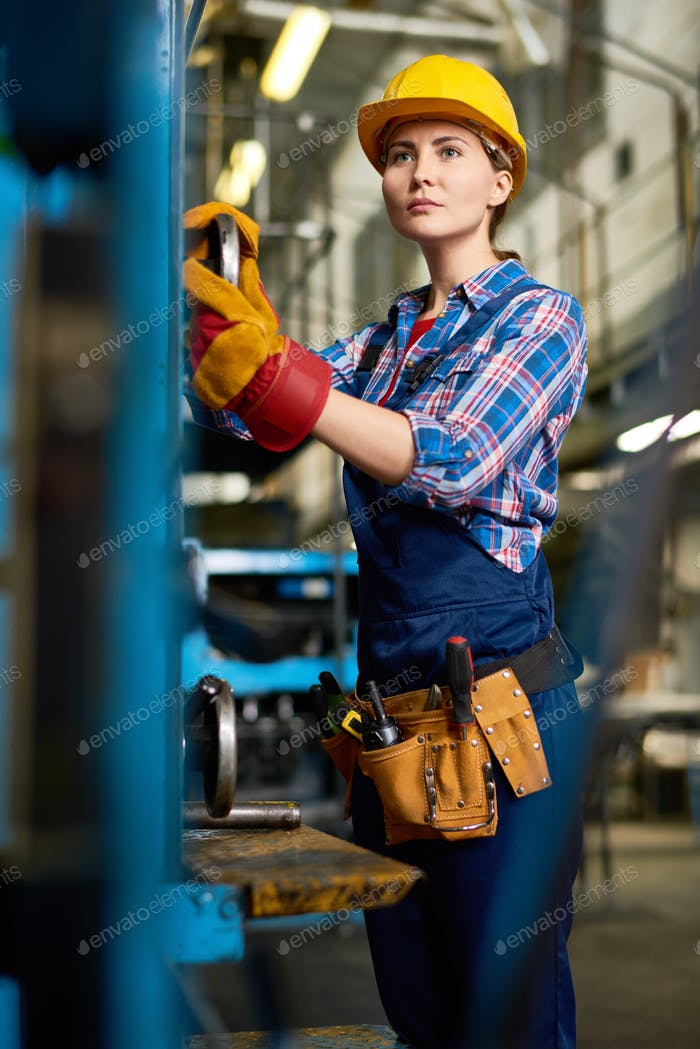 Young Woman Operating Machines in  Factory Workshop