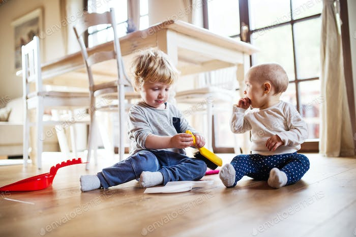 Two toddlers with brush and dustpan at home.