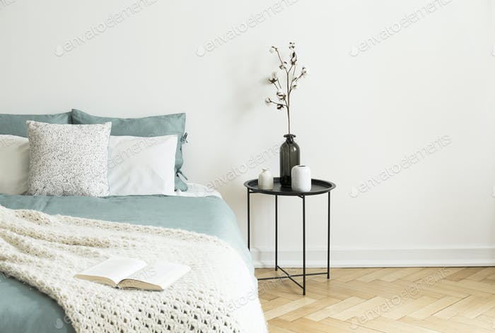 Black Table Next To Bed With Green Sheets Pillows And Knit Blan