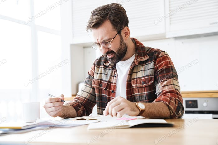Portrait of young bearded displeased man working with notes at home