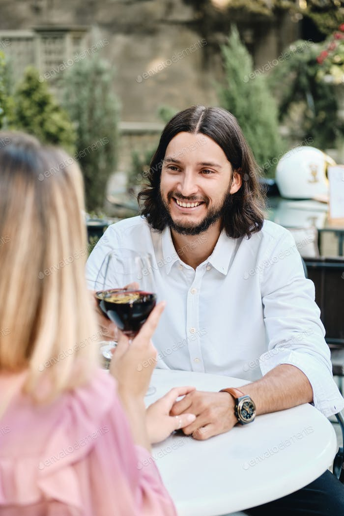 Attractive latin man with glass of wine joyfully looking at girlfriend on romantic date in cafe