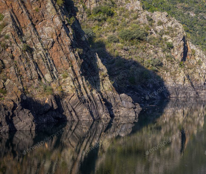 The cliffs of shale rock of the canyon are reflected in the stil