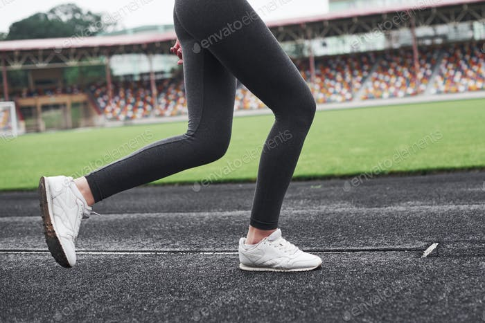 Picture of the legs only. Girl running on the track in the stadium at daytime