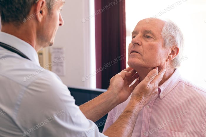 Male doctor checking senior man in clinic at retirement home