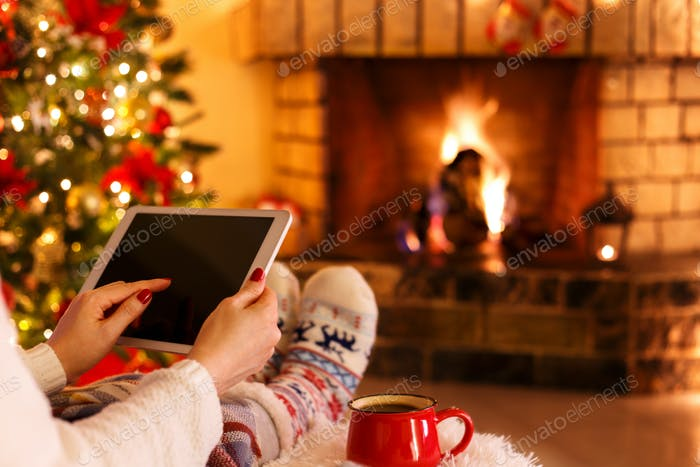 Woman with tablet by fire place