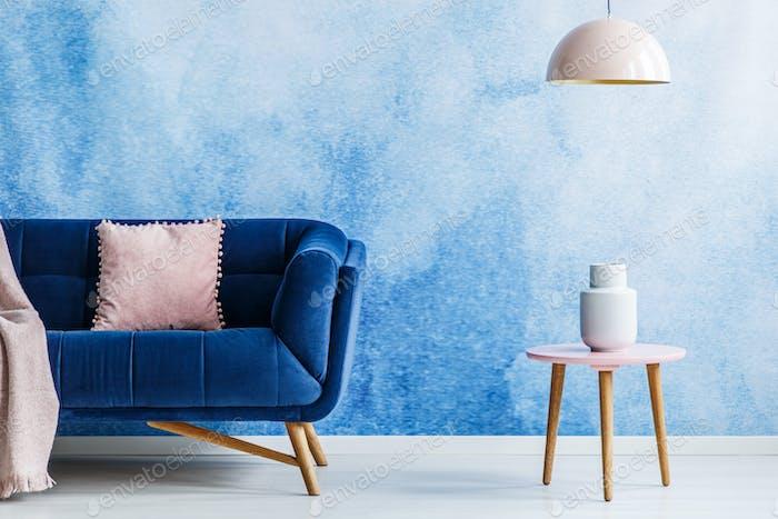 Blaues und weiches rosa minimalistisches Wohnzimmer. Interieur mit dunkel